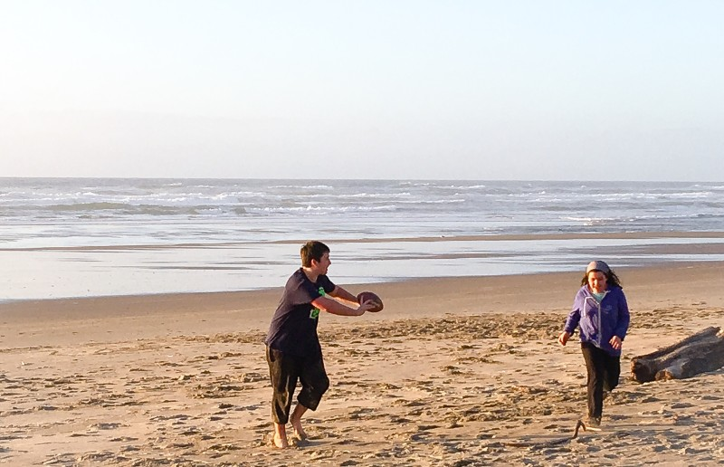 Kids playing football at beach